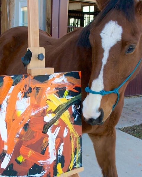 Metro Meteor poses with one of his paintings