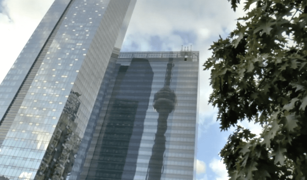 The CN Tower (reflected in an adjacent building) is one of the many things to do during a visit to Toronto