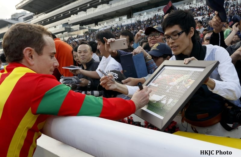 Ryan Moore, winner of the Hong Kong Cup aboard Maurice, pauses to sign an autograph for one of the over 100,000 fans in attendance at Sha Tin.