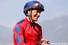 Gary Stevens smiles as he enters the winner's circle